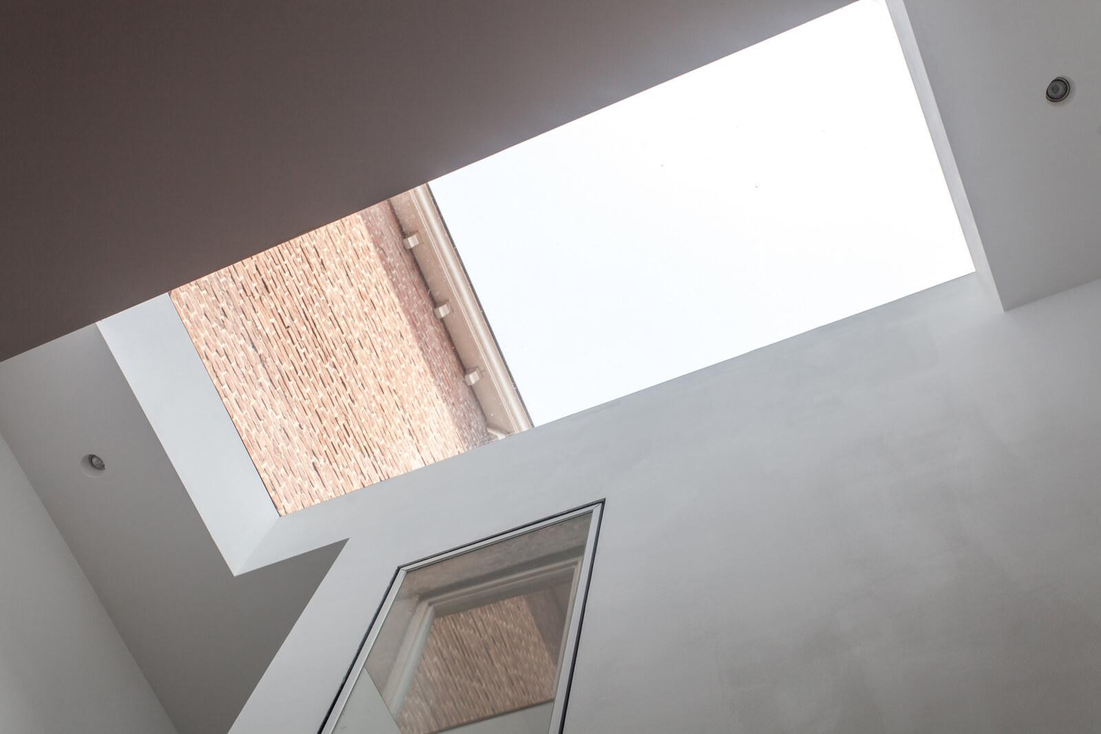 Lumière naturelle dans un immeuble étroit et sombre grâce à une fenêtre de toit